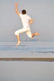 Mann im weißen Kleid springt Stockfotos