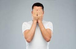 Mann im weißen T-Shirt, das sein Gesicht mit den Händen bedeckt Lizenzfreies Stockbild