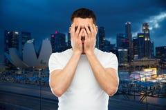 Mann im weißen T-Shirt, das sein Gesicht mit den Händen bedeckt Lizenzfreies Stockfoto