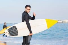 Mann im Wetsuit mit einem Surfbrett an einem sonnigen Tag Lizenzfreie Stockbilder