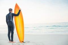 Mann im Wetsuit mit einem Surfbrett an einem sonnigen Tag Stockfoto