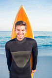 Mann im Wetsuit mit einem Surfbrett an einem sonnigen Tag Lizenzfreies Stockfoto