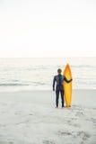Mann im Wetsuit mit einem Surfbrett an einem sonnigen Tag Stockbilder