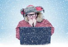 Mann im Winter kleidet die Erwärmung seiner Hände beim Sitzen vor Laptop Kälte, Schnee, Blizzard Stockfotografie