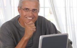 Mann im Wohnzimmer mit Computer lizenzfreie stockfotografie