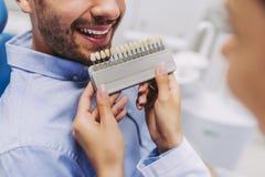 Mann im Zahnarztstuhl, der Zahnimplantate wählt lizenzfreie stockfotografie