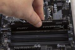 Mann installiert ein Wut-Gedächtnis RAM Module DDR 4 DIMM 16 GB Kingston HyperX in den Schlitz auf die Motherboardnahaufnahme stockfotos