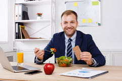 Mann isst gesunden Business-Lunch im modernen Büroinnenraum zu Mittag lizenzfreies stockbild
