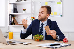 Mann isst gesunden Business-Lunch im modernen Büroinnenraum zu Mittag lizenzfreie stockfotografie