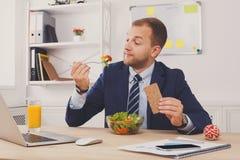 Mann isst gesunden Business-Lunch im modernen Büroinnenraum zu Mittag stockfotografie