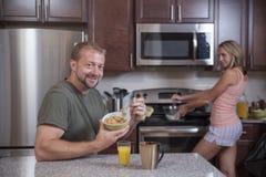Mann isst Getreide, während Dame Frühstück macht Stockfotos