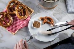 Mann isst weiße Wurst Münchens mit Messer und Gabel, süßen Senf und Brezel und entfernt Wurst richtig aus Darm heraus lizenzfreies stockbild