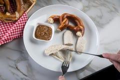 Mann isst weiße Wurst Münchens mit Messer und Gabel, süßen Senf und Brezel und entfernt Wurst richtig aus Darm heraus stockbild