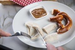 Mann isst weiße Wurst Münchens mit Messer und Gabel, süßen Senf und Brezel und entfernt Wurst richtig aus Darm heraus stockfoto