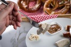 Mann isst weiße Wurst Münchens mit Messer und Gabel, süßen Senf und Brezel und entfernt Wurst richtig aus Darm heraus stockfotos