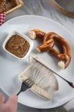 Mann isst wei?e Wurst M?nchens mit Messer und Gabel, s??en Senf und Brezel und entfernt Wurst richtig aus Darm heraus stockbilder