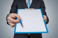 Mann ist, anbietend zeigend und leeres Weißbuch im Klemmbrett mit Stift Stockbild