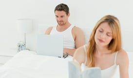 Mann ist auf seinem Laptop, während seine Frau liest Stockbild