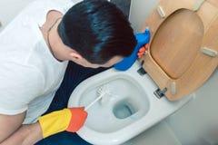 Mann ist ein Stückchen, das die Toilette säubernd geekelt wird lizenzfreies stockfoto