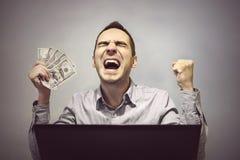 Mann ist glücklich vor dem Computer, 500 Dollar zu halten Lizenzfreie Stockfotos