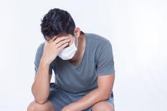 Mann ist kranke und der Abnutzung hygienische Maske und Kopfschmerzen lizenzfreies stockbild