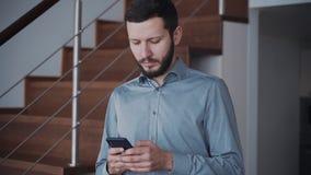 Mann ist, plaudernd stehend und mit den Leuten, die zu Hause Smartphone für Geschäft und Kommunikation verwenden stock video footage