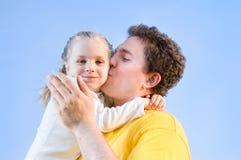 Mann küßt seine Tochter Stockbild
