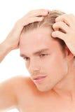 Mann kümmern sich um seinem Haar Stockfotografie