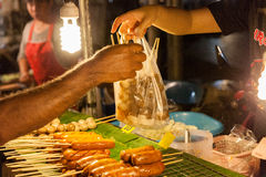 Mann kauft Fleischklöschen am Sonntags-Markt Stockfotografie