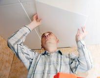 Mann klebt Deckenfliese an der Küche Stockbild