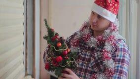 Mann kleidet schönen kleinen glühenden Weihnachtsbaum stock video footage