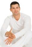 Mann kleidete im weißen Sitzen auf dem Fußboden an Lizenzfreie Stockfotografie