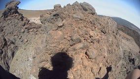 Mann klettert an der Spitze eines Hügels stock video footage