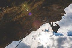Mann klettert einen Felsen stockfotografie