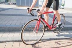 Mann kommt unten vom Vorhang auf einem roten Rennrad der Stadt Ein Radfahrer, der um die Stadt radfährt stockfotografie