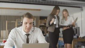 Mann konsultiert Kunden telefonisch und sitzt in einem B?ro in der Tageszeit, zwei Frauen auf Unsch?rfehintergrund stock video footage