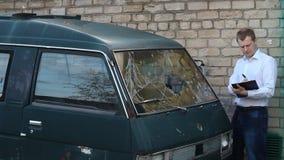 Mann kontrolliert einen defekten Autokleinbus, Versicherung stock footage