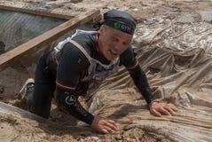 Mann kriecht auf ein Verschanzung mit Sand und Wasser Stockfotos