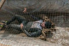 Mann kriecht auf ein Verschanzung mit Sand und Wasser Lizenzfreie Stockfotos