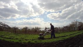 Mann kultiviert den Boden im Garten mit einem Pfl?ger und bereitet den Boden f?r das S?en vor stock video footage