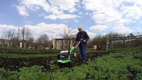 Mann kultiviert den Boden im Garten mit einem Pfl?ger und bereitet den Boden f?r das S?en vor stock video