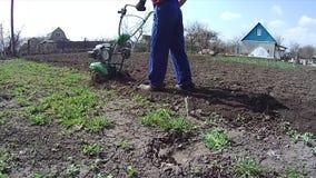 Mann kultiviert den Boden im Garten mit einem Pfl?ger und bereitet den Boden f?r das S?en vor stock footage