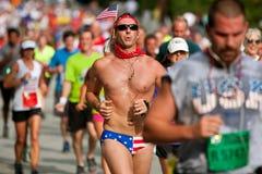 Mann lässt Atlanta-Straßenrennen laufen, das patriotischen Bikini trägt stockfoto
