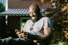 Mann lacht Lesetextnachricht im Garten Lizenzfreie Stockfotos