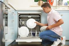 Mann-Laden-Spülmaschine In Kitchen lizenzfreie stockbilder