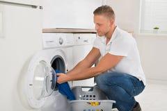 Mann-Laden-Waschmaschine mit Kleidung stockfotografie