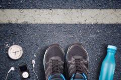 Mann-Laufschuhe und Laufausrüstung auf Asphalt Laufendes Training auf harten Oberflächen Läufer-Ausrüstungsstoppuhr und Musikspie Stockbild