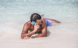 Mann legt auf den Strand und spricht per Telefon Lizenzfreie Stockfotos