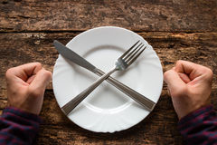 Mann lehnt ab, Löffel und Gabel auf einer Platte zu essen, die in Form eines Kreuzes gestapelt wird Stockfotografie