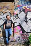 Mann lehnt sich auf Wand mit Graffiti Lizenzfreie Stockfotos